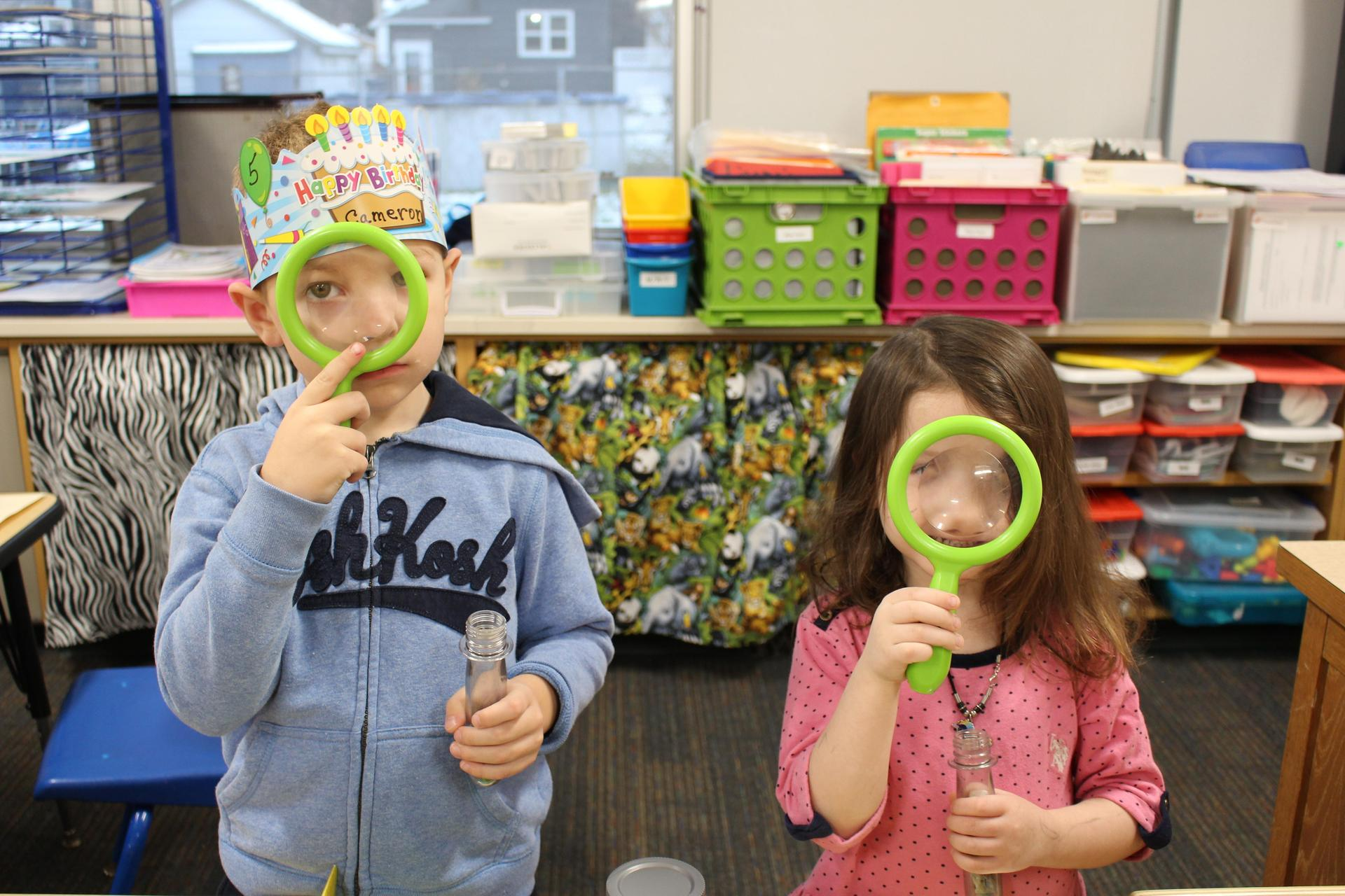 boy and girl hold magnifying glass up to face