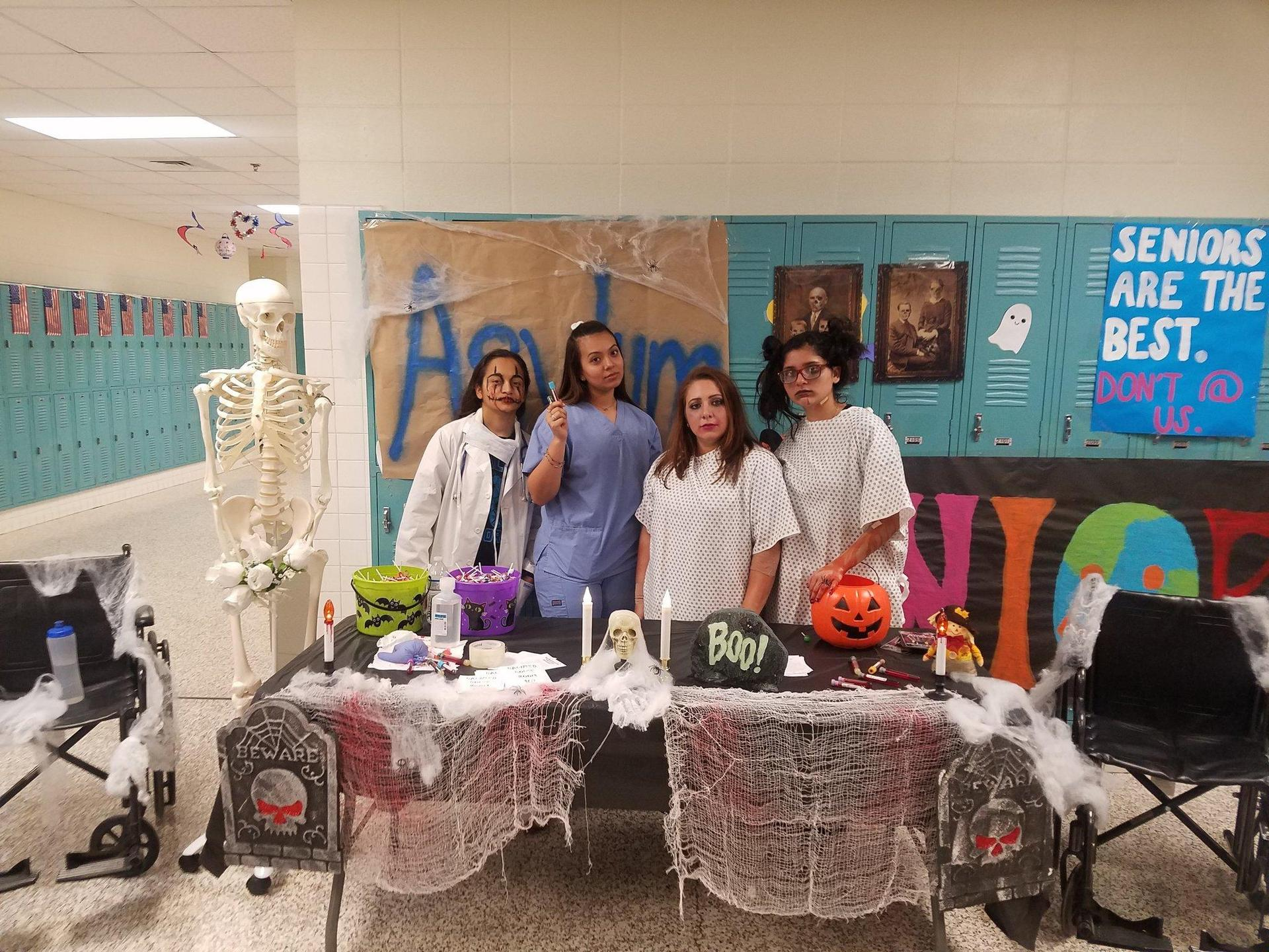 students in medical attire in front of Halloween display