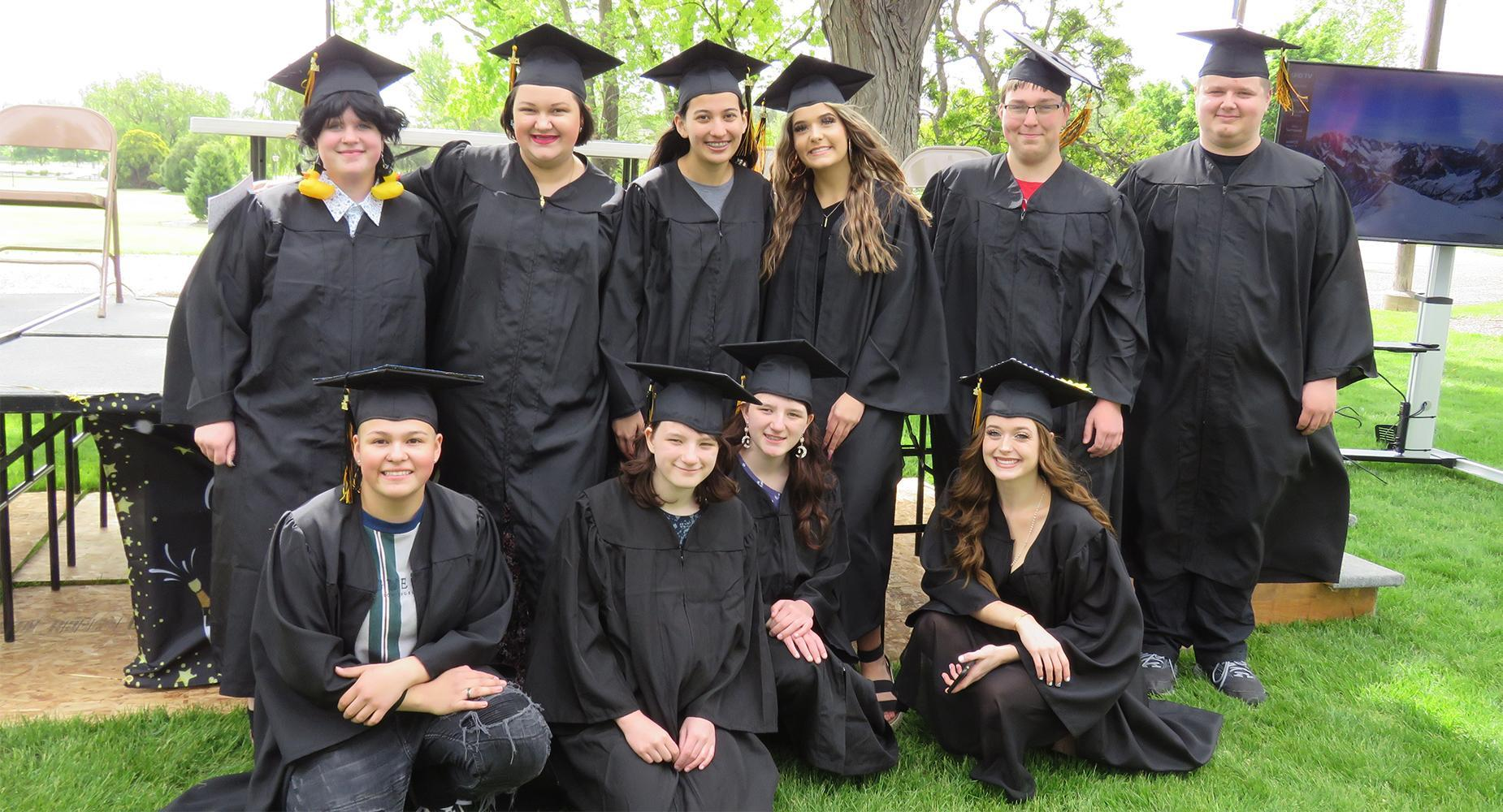 TVLA Graduates pose for a group photo wearing caps and gowns.
