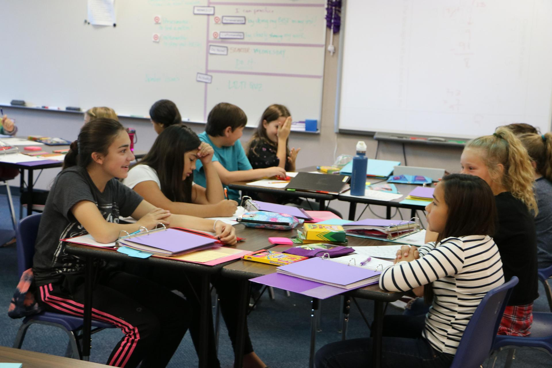 Students discuss and smile in a middle school math classroom.