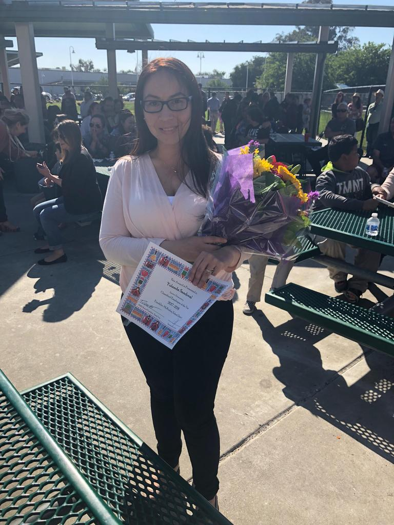 yolanda sandoval, classified employee of the year, poses with flowers