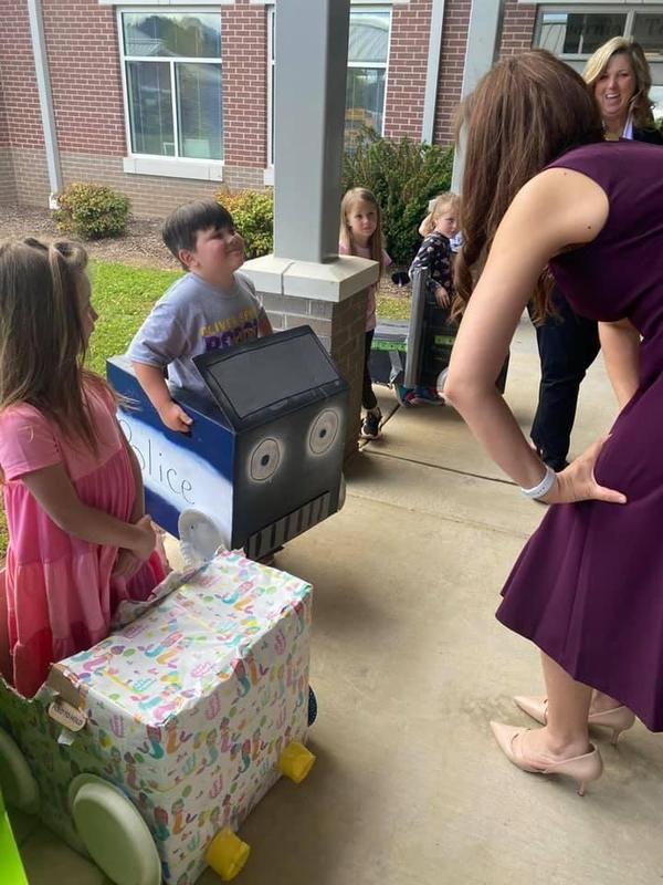 Dr. Schwinn talks to student about homemade box car