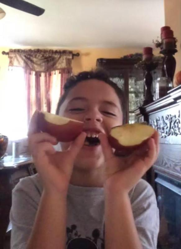 Student holding up a split apple