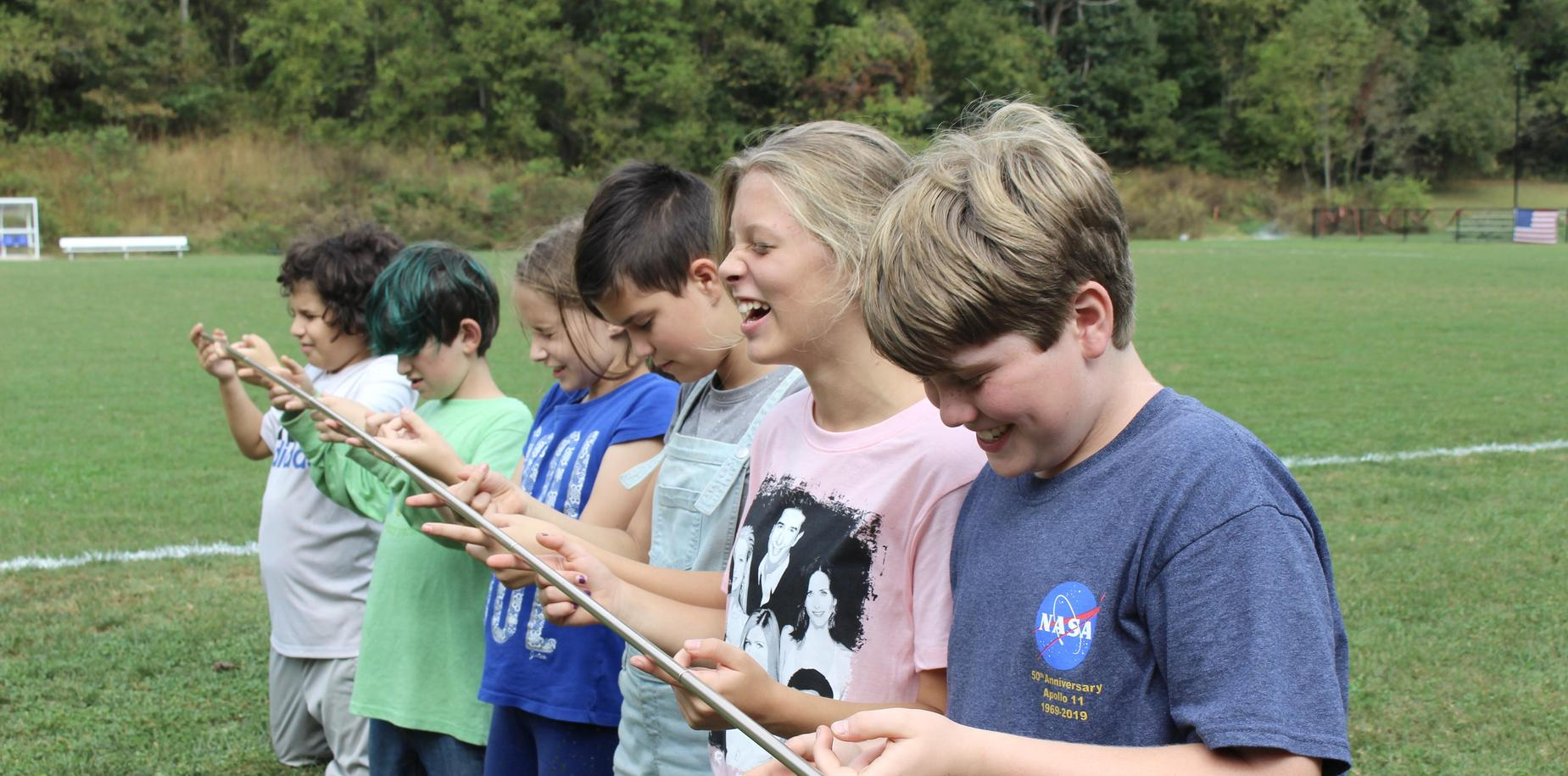 Students stand in a row and balance a rod on their hands, eyes closed and laughing.