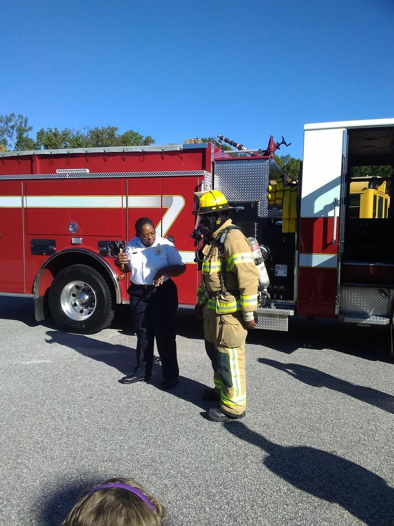 Fire and Life Safety Educator talks to students about a firefighter's gear.