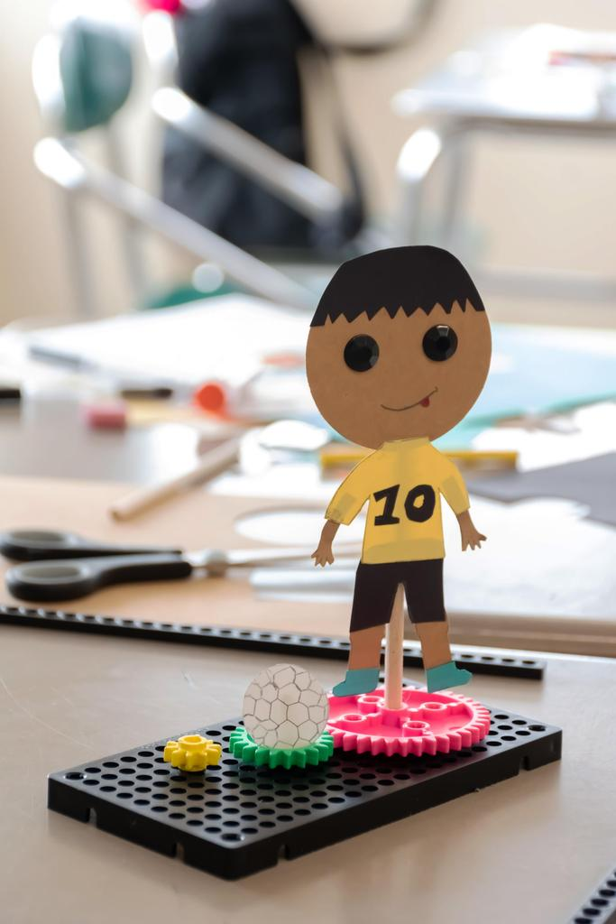 An up-close view of a kinetic sculpture with a cutout of a boy in a 'Number 10' jersey