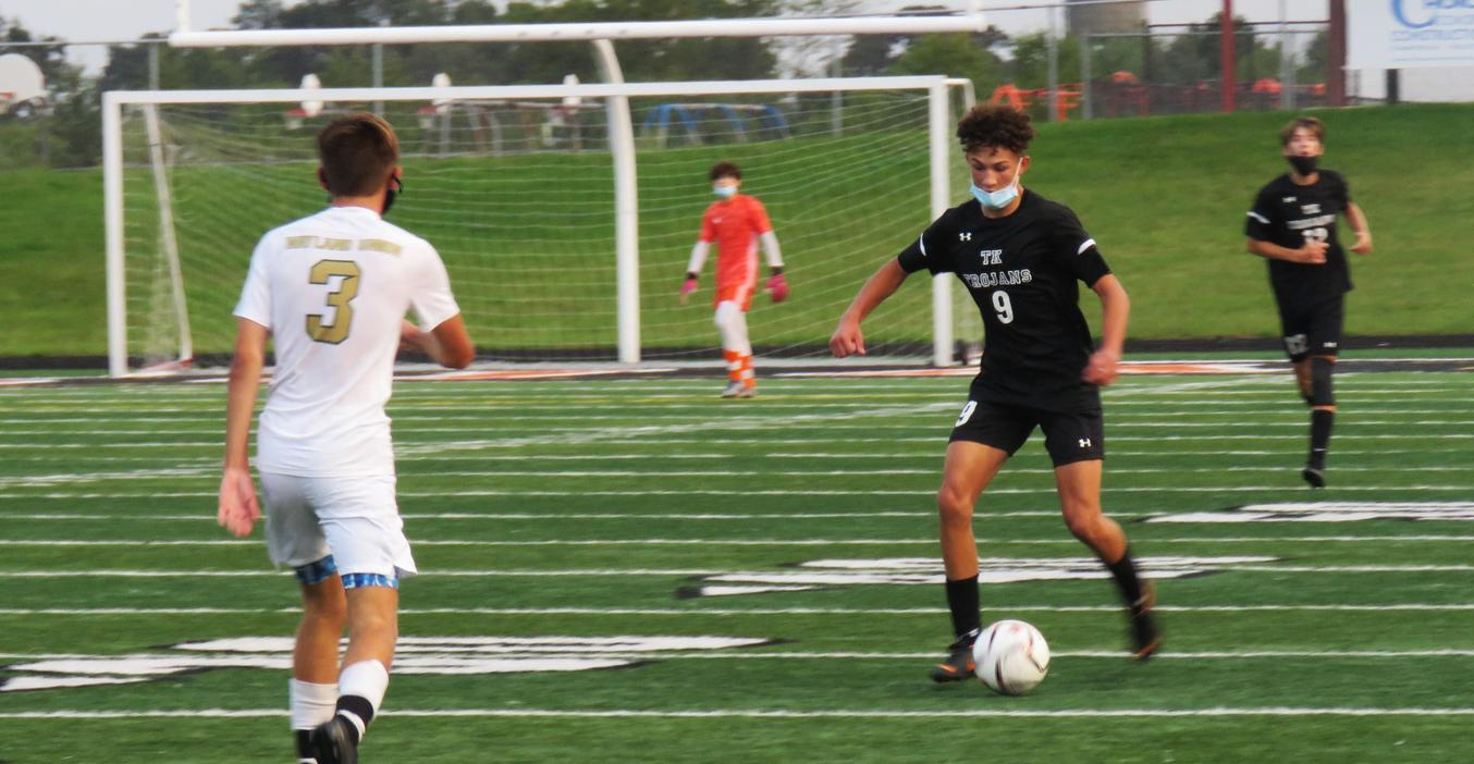A TKHS soccer player dribbles the ball up the field.