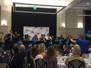 a photo of the Kids' Orchestra Wind Ensemble performing at the annual breakfast