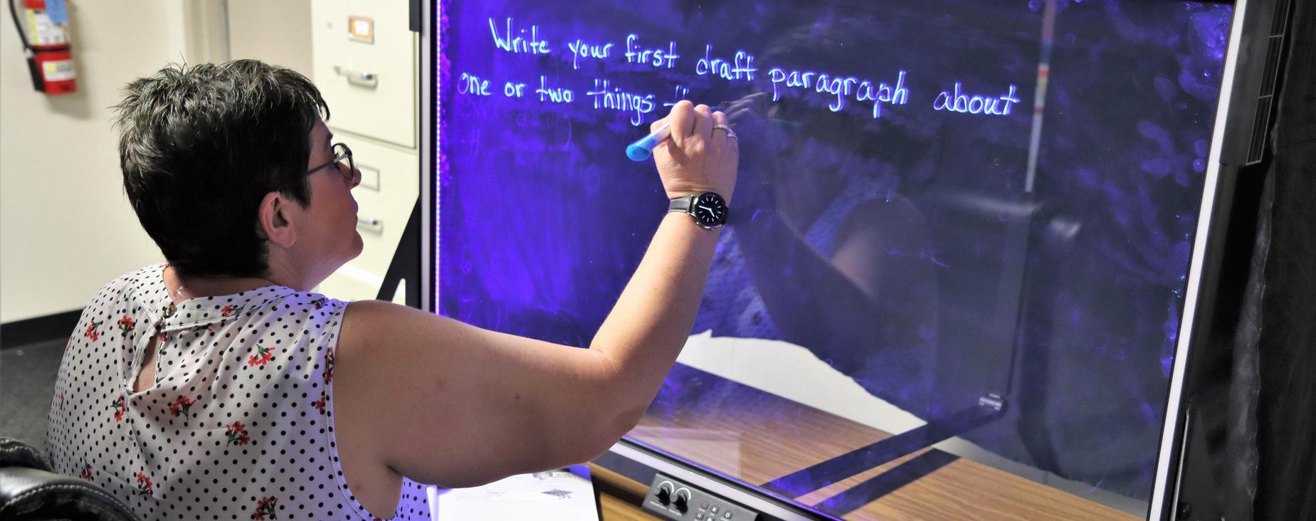 Teacher writing on eGlass surface