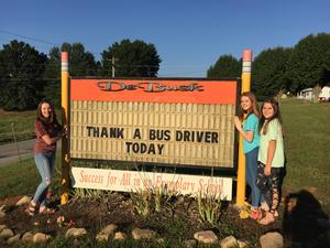 Students standing out front with the DeBusk Elementary sign reading