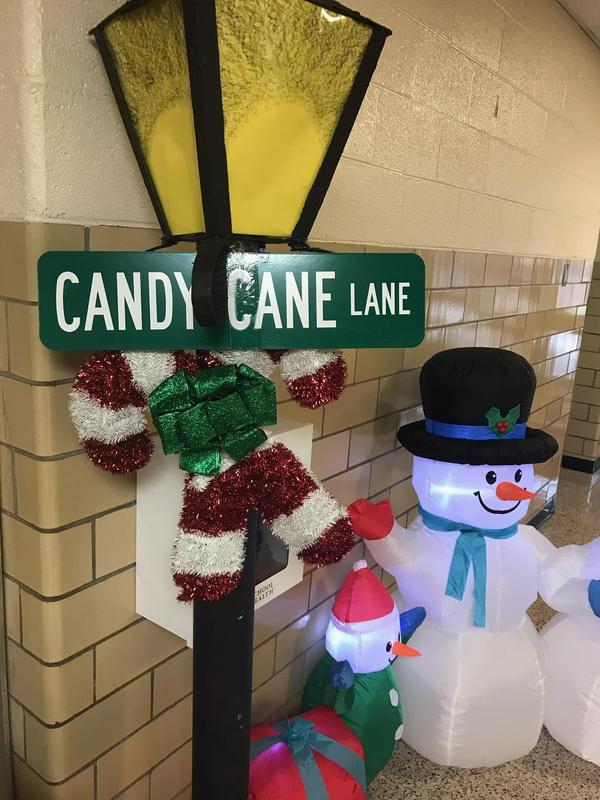 Inflatable snowman by lamp post with streetsign for