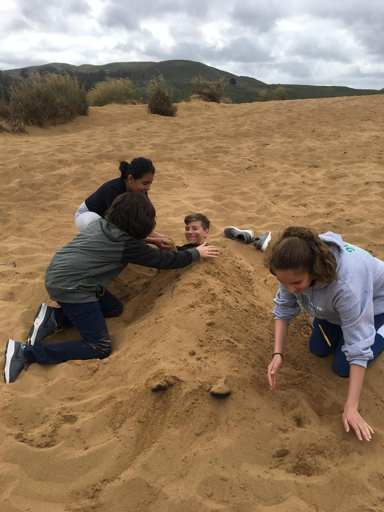 boy being buried in sand.