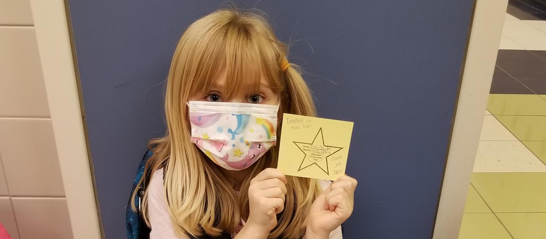 girl wearing a mask showing the star she earned