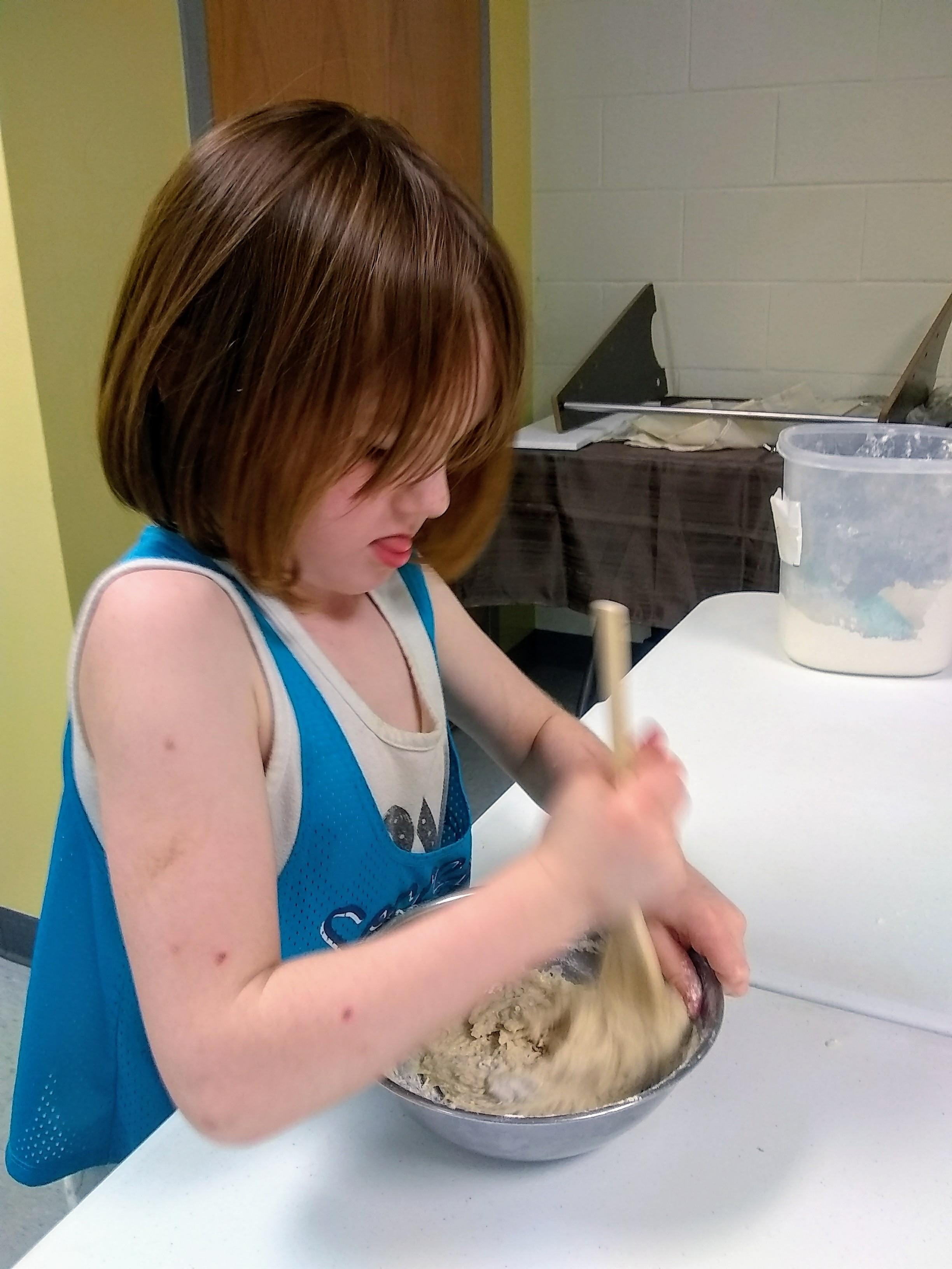child mixing dough